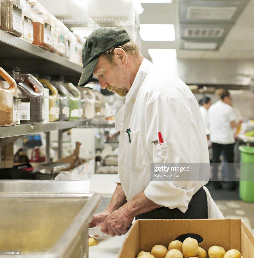 Chef chops potatoes : Stock Photo