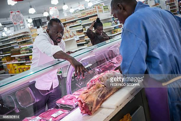 Chef Christian Baby Yumbi owner of the 'Resource' restaurant explains to the local butcher the cuts he needs for his kitchen on February 19 2015 in...