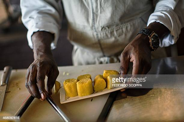 Chef Christian Baby Yumbi owner of the 'Resource' restaurant works in his open air kitchen on February 19 2015 in Kinshasa Baby Yumbi moved his...
