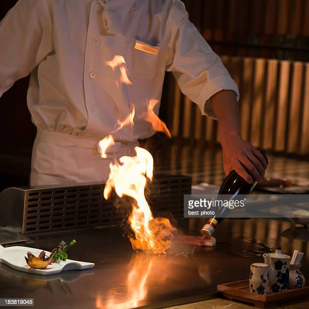 Chef cooking food on an iron griddle, teppanyaki-style