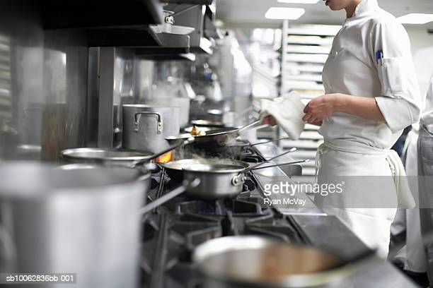 Chef cooking in commercial kitchen, mid section
