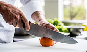 Close-up of a chef cooking in the kitchen of a restaurant and chopping vegetables