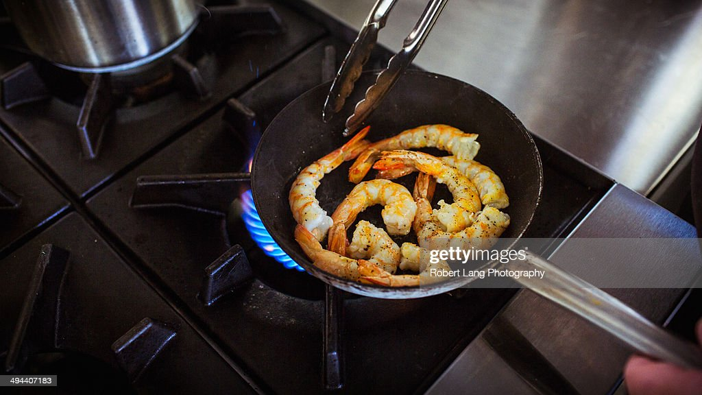 Chef cooking prawns in a skillet pan