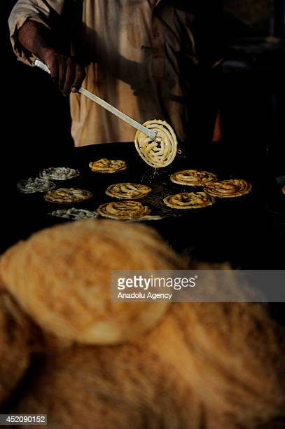 A chef cooks jalebi sweet traditional Pakistani food during Ramadan month in Islamabad Pakistan on 2 July 2014 Traditional foods are in demand on...