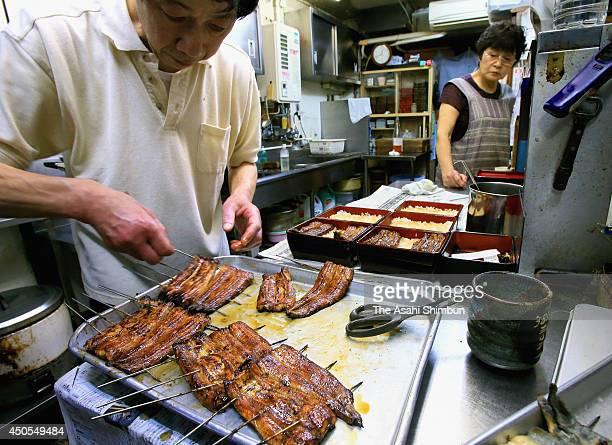 A chef cooks Nihon Unagi or Japanese eel at a restaurant on June 12 2014 in Tokyo Japan The Japanese eel has been named an endangered species on an...
