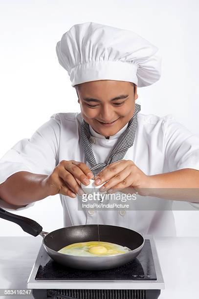 Chef cracking egg into frying pan