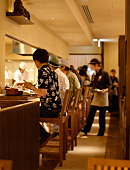 A soft focused shot of patrons eating at the counter of a Japanese restaurant, flanked by chefs and waitress