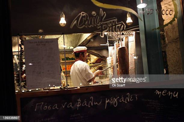 A chef cuts a kebab in a restaurant in the Psiri district on February 19 2012 in Athens Greece Following a meeting on Wednesday finance ministers...