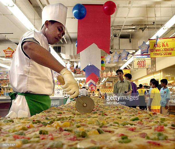 A chef cuts part of the longest pizza displayed at a supermarket in Jakarta 21 September 2003 The 50meter pizza was cooked by 20 chefs in two days...