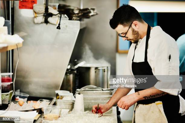 Chef cutting and tying twine on bowls with egg white in restaurant kitchen