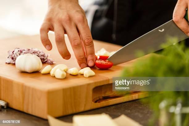 Koch-schneiden-Cherry-Tomate auf Schneidebrett