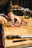 Chef cutting filet on a wooden board