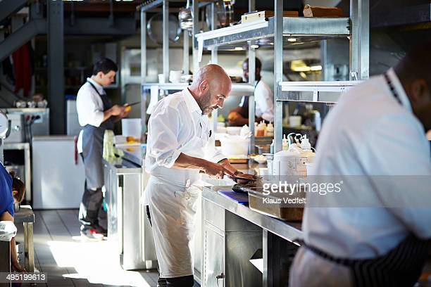 Chef cutting fish at kitchen in restaurant