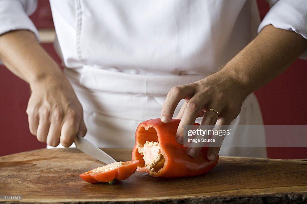 Chef cutting pepper