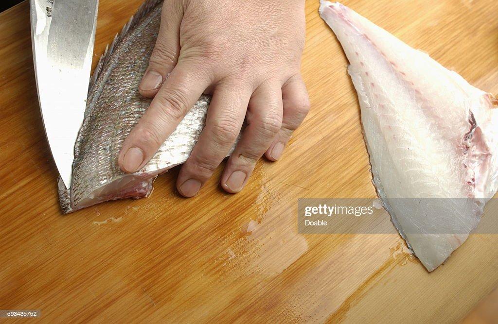 Chef cutting sea bream, close up