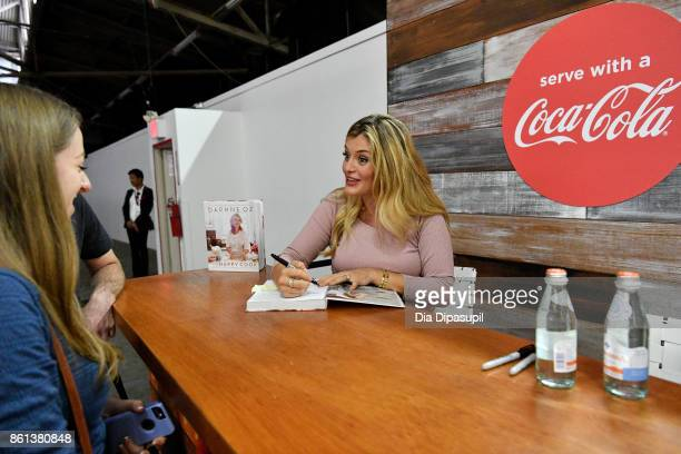 Chef Daphne Oz signs her cookbook The Happy Cook at attends the Food Network Cooking Channel New York City Wine Food Festival presented by CocaCola...