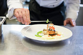 Chef decorating a meal made of fish
