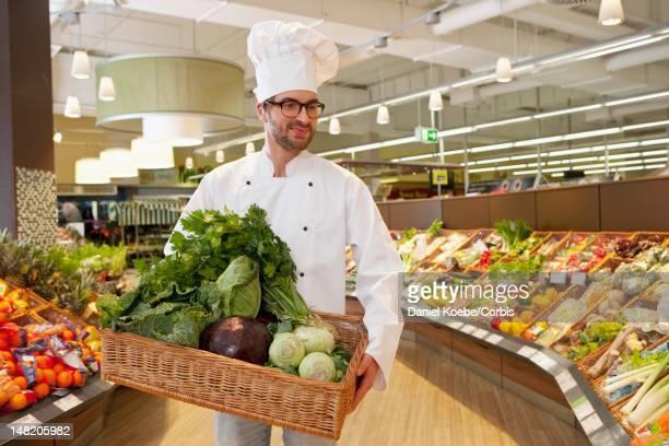 Chef delivering basket with vegetables in supermarket