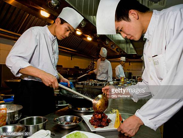 Chef dressing plate in commercial kitchen