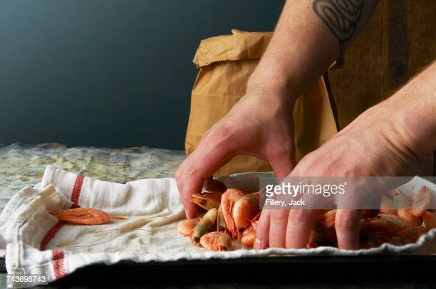 A chef filling a paper bag with cooked prawns