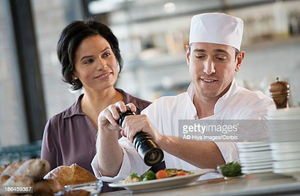 Chef finishing dish in kitchen