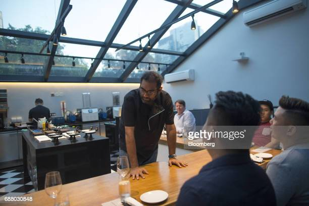 Chef Gaggan Anand center interacts with customers sitting at the chef's table inside the research and development kitchen at Gaggan restaurant in...