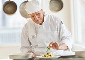 Front view of mature male chef garnishing dish at counter in commercial kitchen