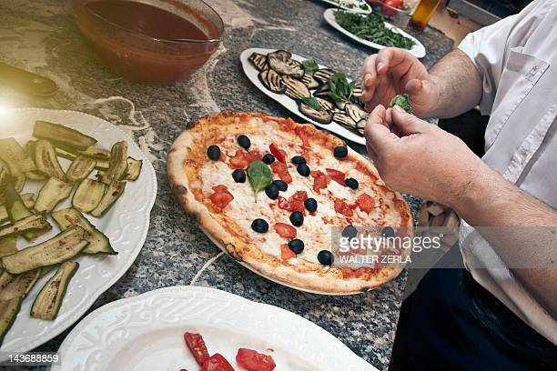 Chef garnishing pizza in kitchen