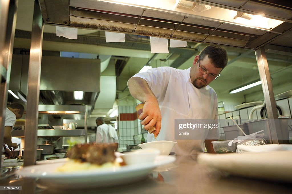 Chef garnishing plates at the pass : Stock Photo