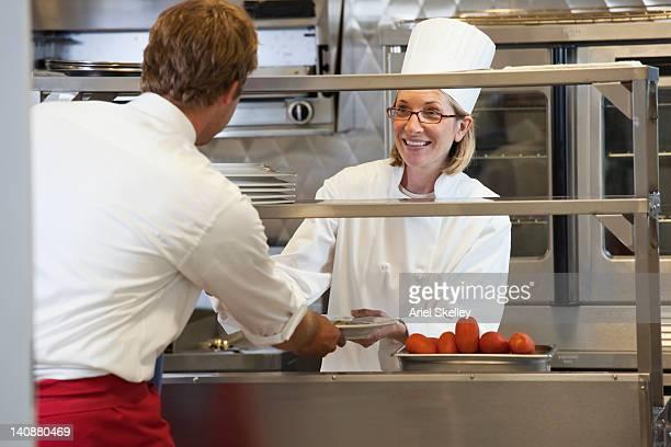 Chef handing food to server in restaurant kitchen