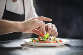 Close up portrait of chef hands preparing vegetable salad