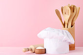 Chef hat with cooking cutlery and flour on pink background