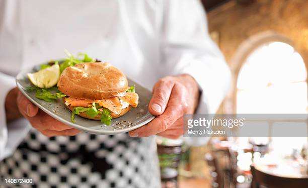 Chef holding bagel with Scottish smoked salmon and cream cheese