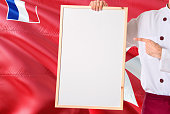 Chef holding blank whiteboard menu on Wallis And Futuna flag background. Cook wearing uniform pointing space for text.