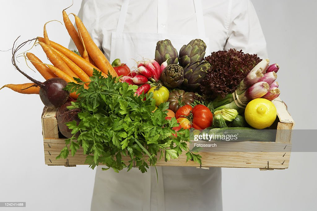 Chef holding box of vegetables (mid section) : Stock Photo