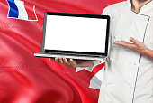 Chef holding laptop with blank screen on Wallis And Futuna flag background. Cook wearing uniform and pointing laptop for copy space.