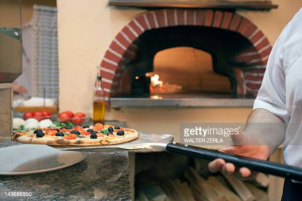 Chef holding pizza on spatula