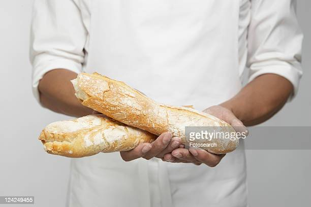 Chef holding two pieces of baguette (mid section)