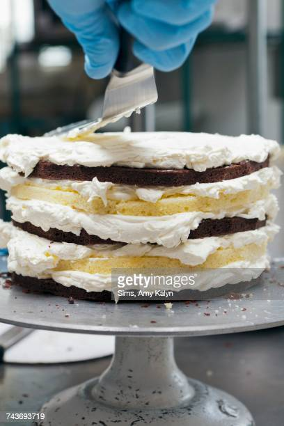A chef icing a layer cake with frosting