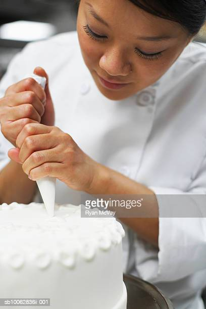 Chef icing cake, close-up