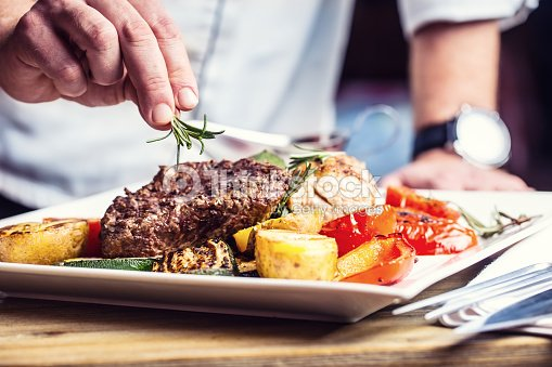 Chef in hotel or restaurant kitchen cooking only hands. : Stock Photo