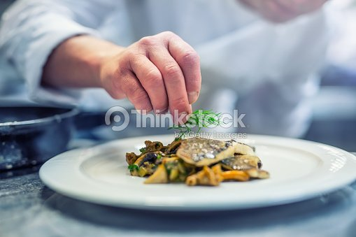 Chef in hotel or restaurant kitchen cooking, only hands. Prepared fish steak with dill decoration : Stock Photo