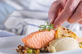 Chef in hotel or restaurant kitchen cooking, only hands. Prepared salmon steak with dill decoration.
