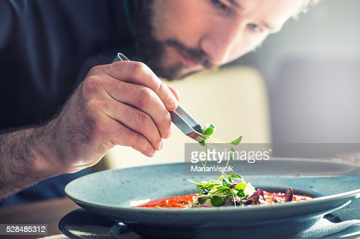 Chef in hotel restaurant kitchen cooking, only hands.Preparing tomato soup : Stock Photo