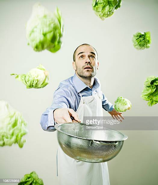 Chef in Kitchen with Lettuce Flying Everywhere