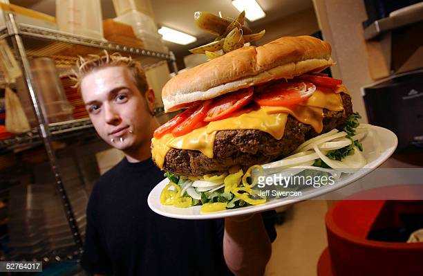 Chef Jeff Zellner of Denny's Beer Barrell hoists one of the establishment's recordbreaking burgers May 5 2005 in the kitchen in Clearfield...