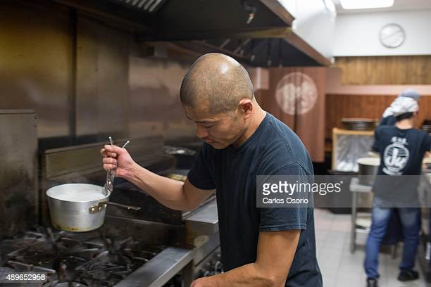 TORONTO ON SEPTEMBER 10 Chef Ju Anzai use a plier like tool to move a hot pot at Izakaya Ju on September 10 2015 For Kitchen Temp series Carlos...