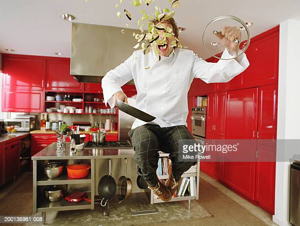Chef jumping in air, contents of pan flying out