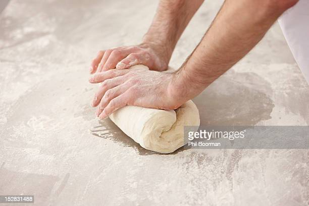 Chef kneading dough in kitchen