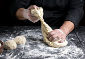 chef kneads dough made of white wheat flour on a black wooden table